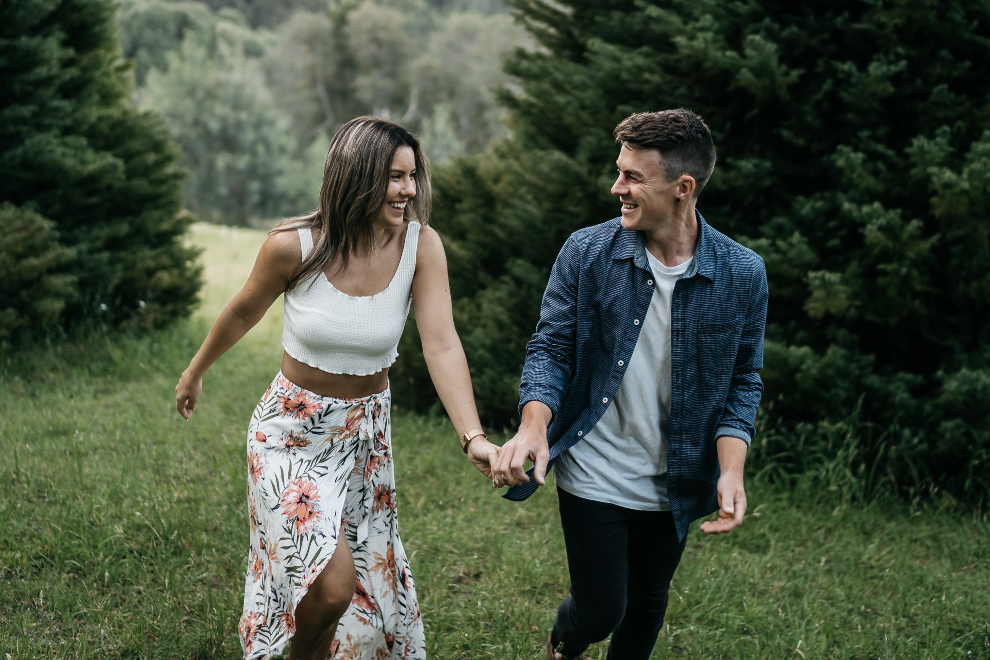 happy couple running in Melbourne forest